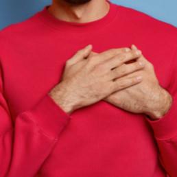 Mann mit rotem Pullover vor blauem Hintergrund, der die Hände vor sein Herz hält
